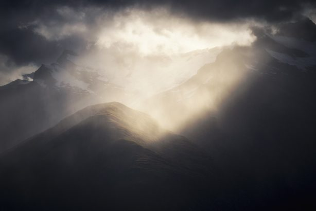 Sunlight beaming thorugh clouds on to a mountain
