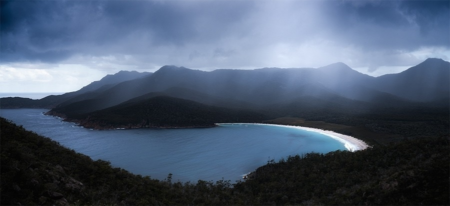 A storm passing over a blue bay