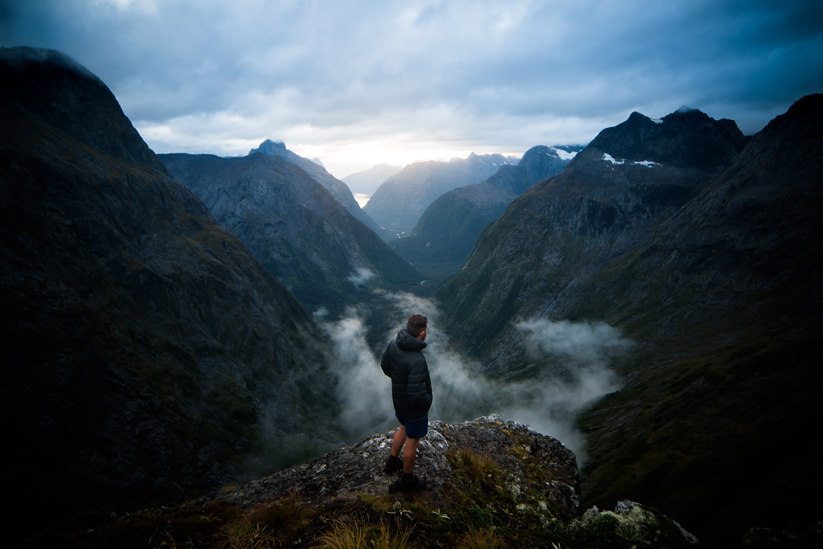 Man standing above foggy valley and mountains