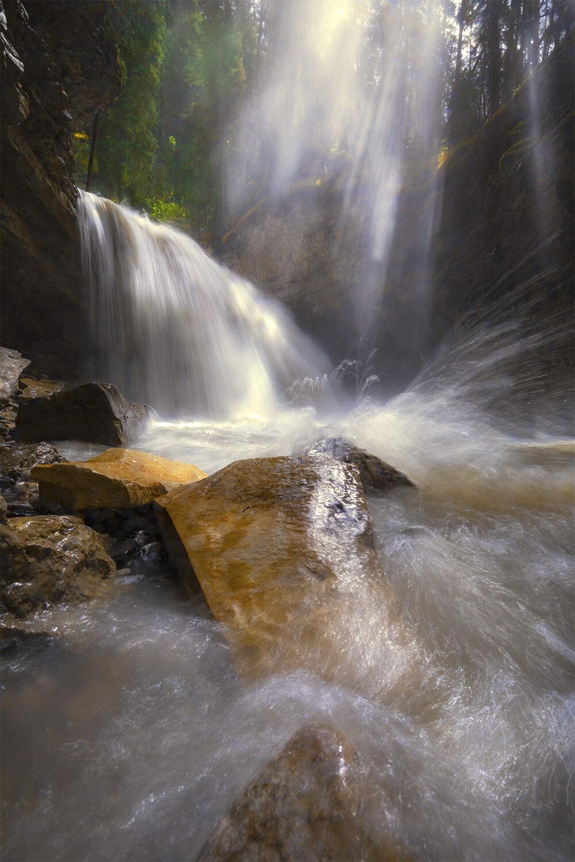 Sunlight cast upon Johnston Canyon waterfall