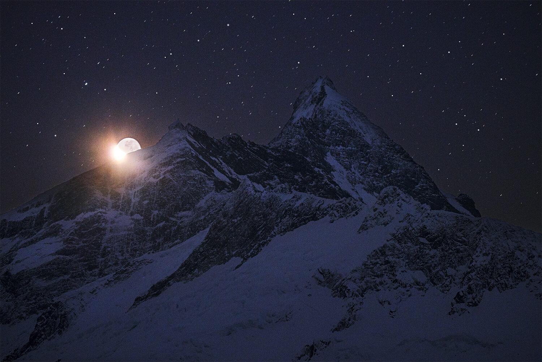 Crescent moon setting behind Mount Aspiring, New Zealand.