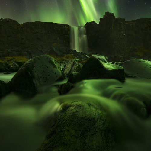 The Northern Lights above a waterfall in Iceland.