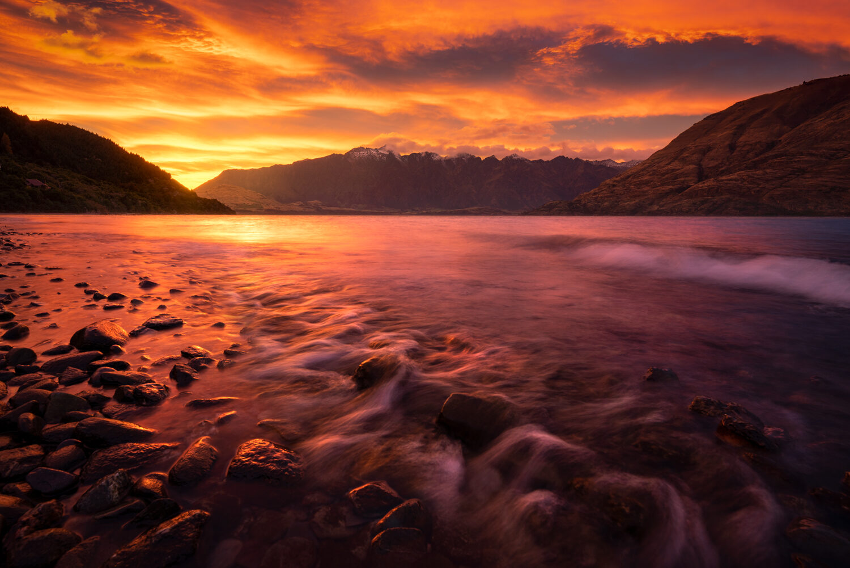 The Remarkables and Lake Wakatipu underneath a colourful sunrise.
