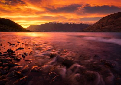 The Remarkables and Lake Wakatipu underneath a colourful sunrise.