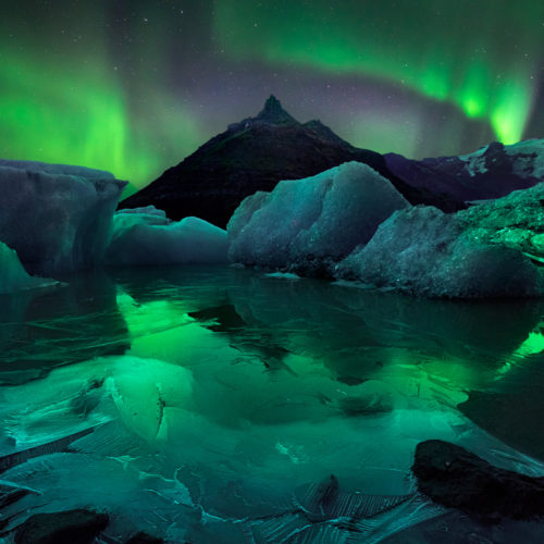 The northern lights in Iceland, dancing above a mountain and glacier landscape. Copyright William Patino