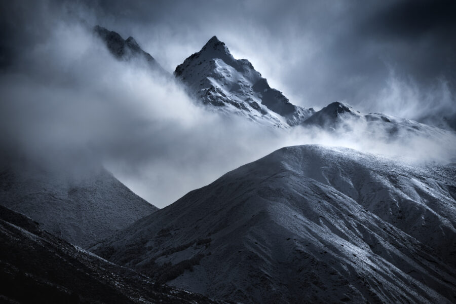 Windswept snow and cloud around the mountains