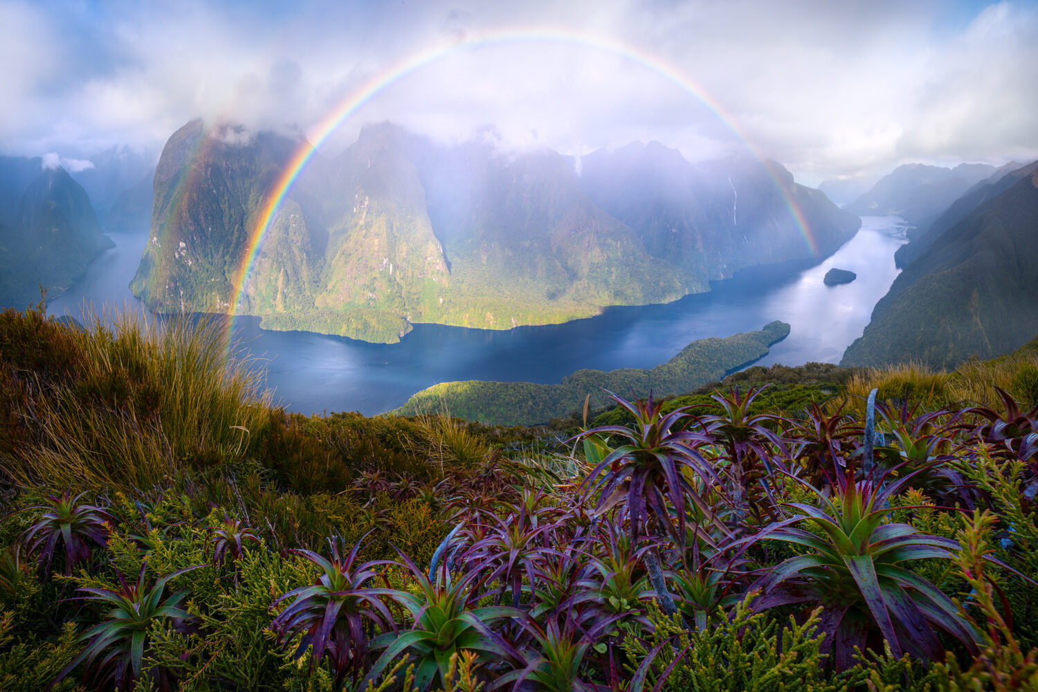 Rainbow spreading across a fiord in New Zealand