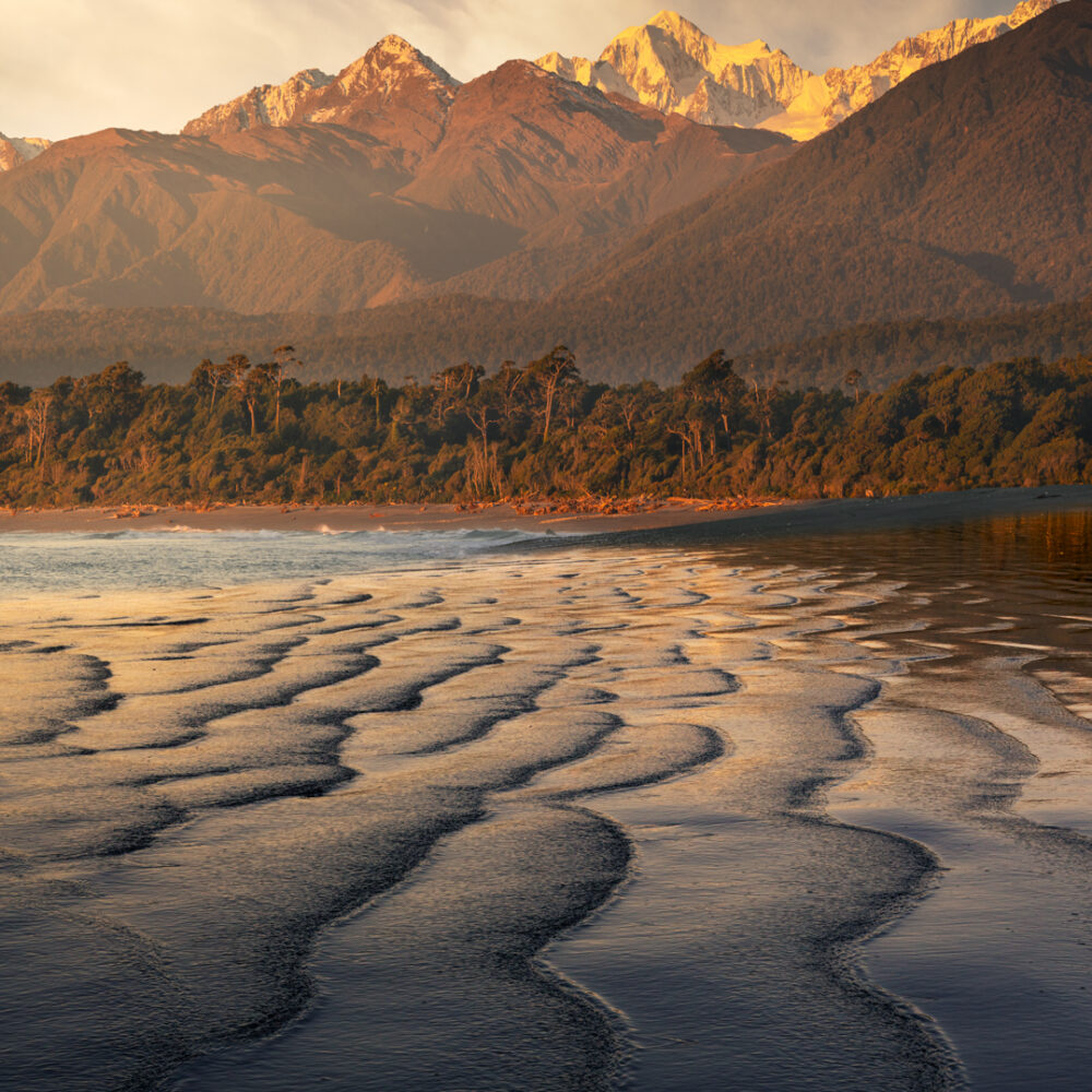 Sand patterns leading to snow capped mountain, New Zealand.