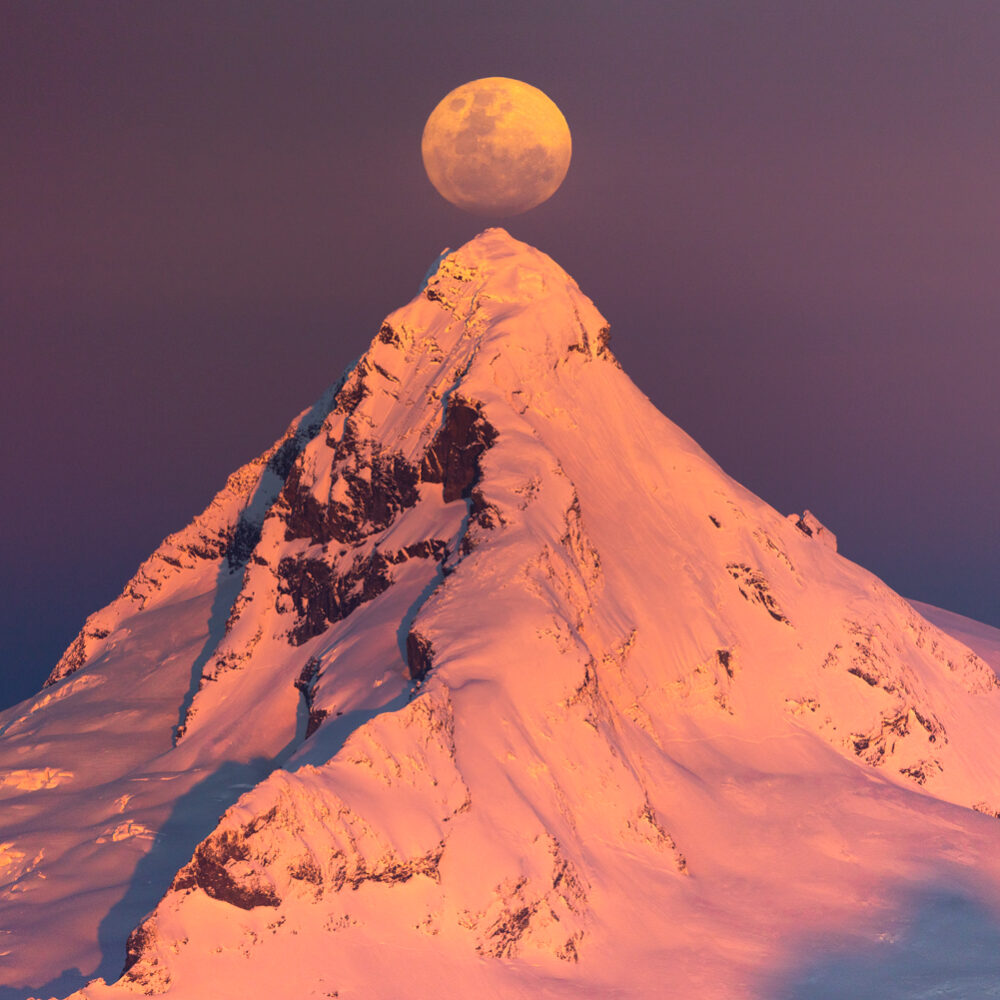 Full moon rise behind mountains